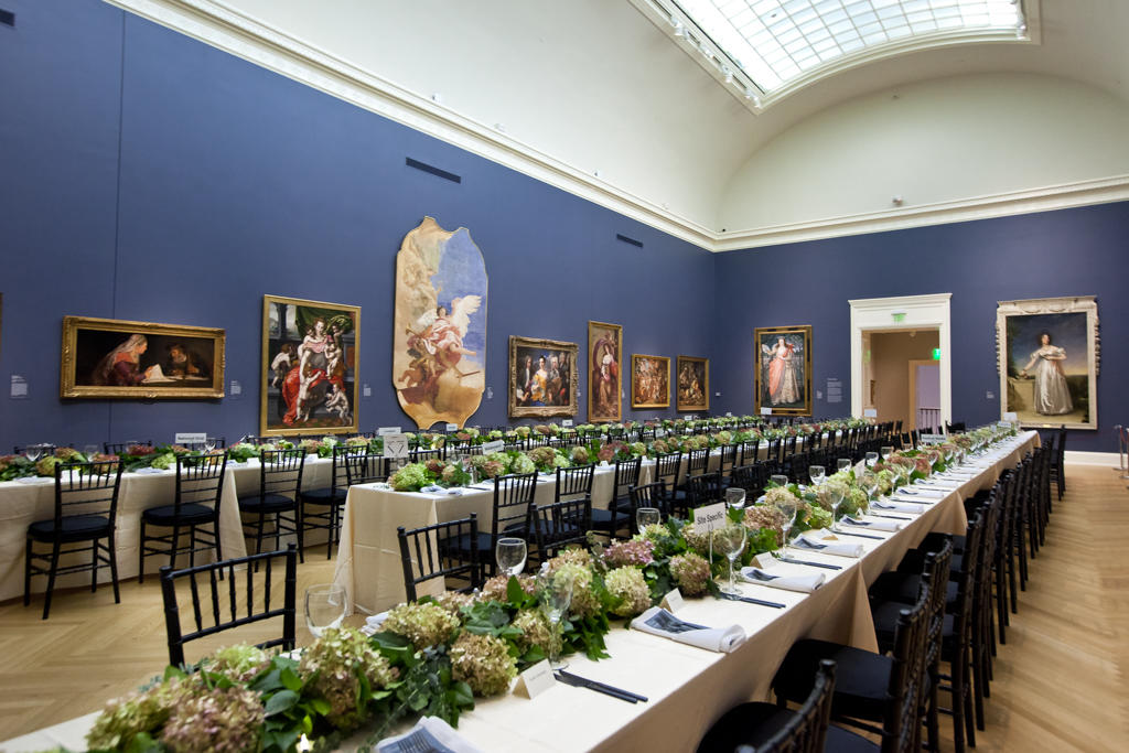 large art gallery with long event tables set for a meal