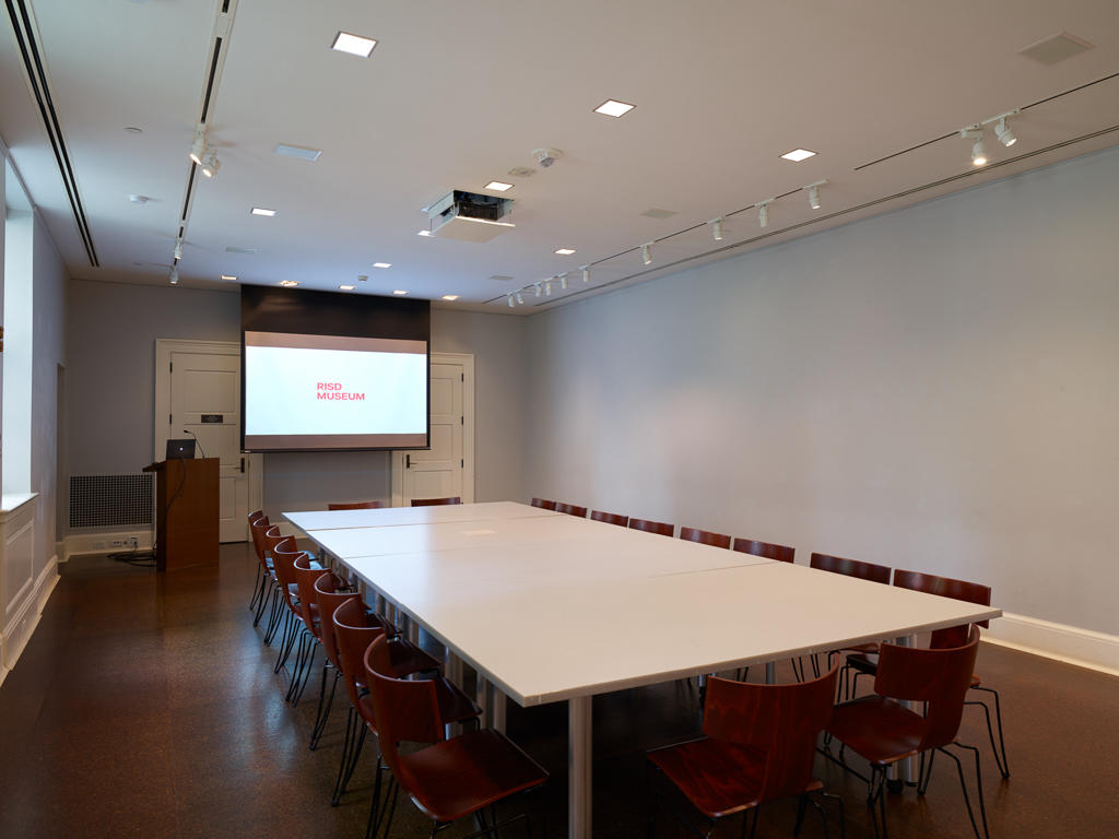 conference room with one large table surrounded with chairs and a projection screen