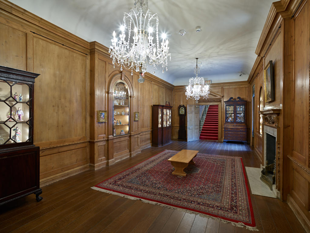 long room with wood-panel walls and two chandeliers