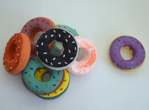 Marofske's cast donuts, primarily plaster and gouache (L), and the original rubber donut dog toy (R).