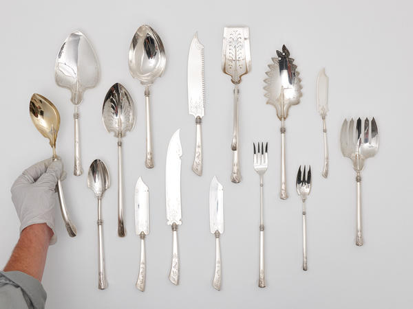 group of flatware with hand placing serving spoon into frame