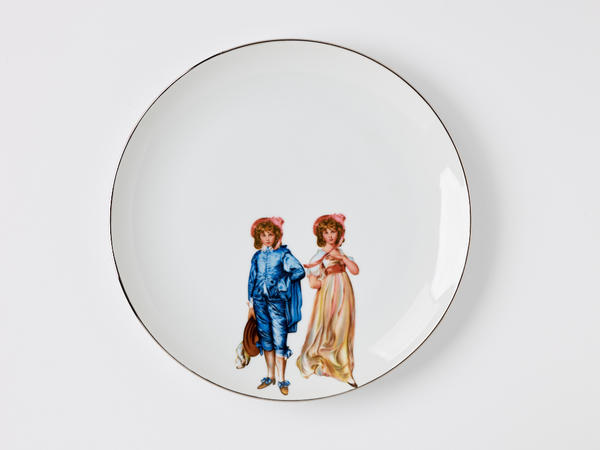 White ceramic plate with two young children dressed in period clothing